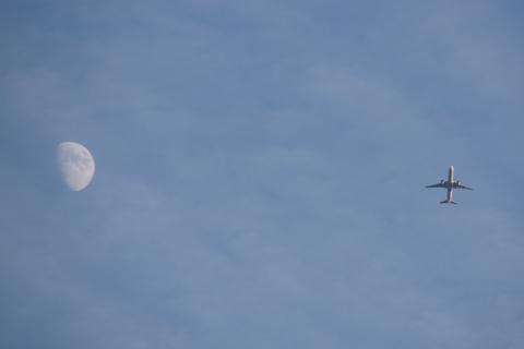 月のそばを飛ぶ飛行機
