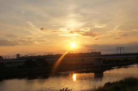 日の入前の夕日と多摩川を渡る東急線