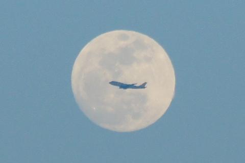 十五夜の前を横切る飛行機
