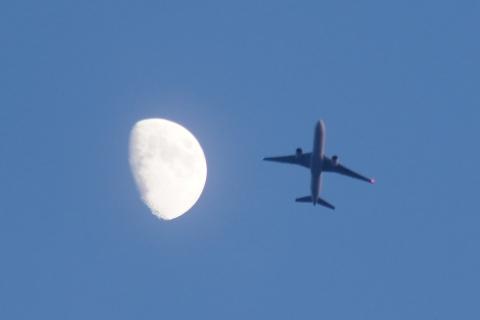 月の横を通る飛行機