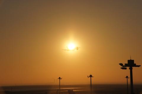 太陽の前を横切る飛行機