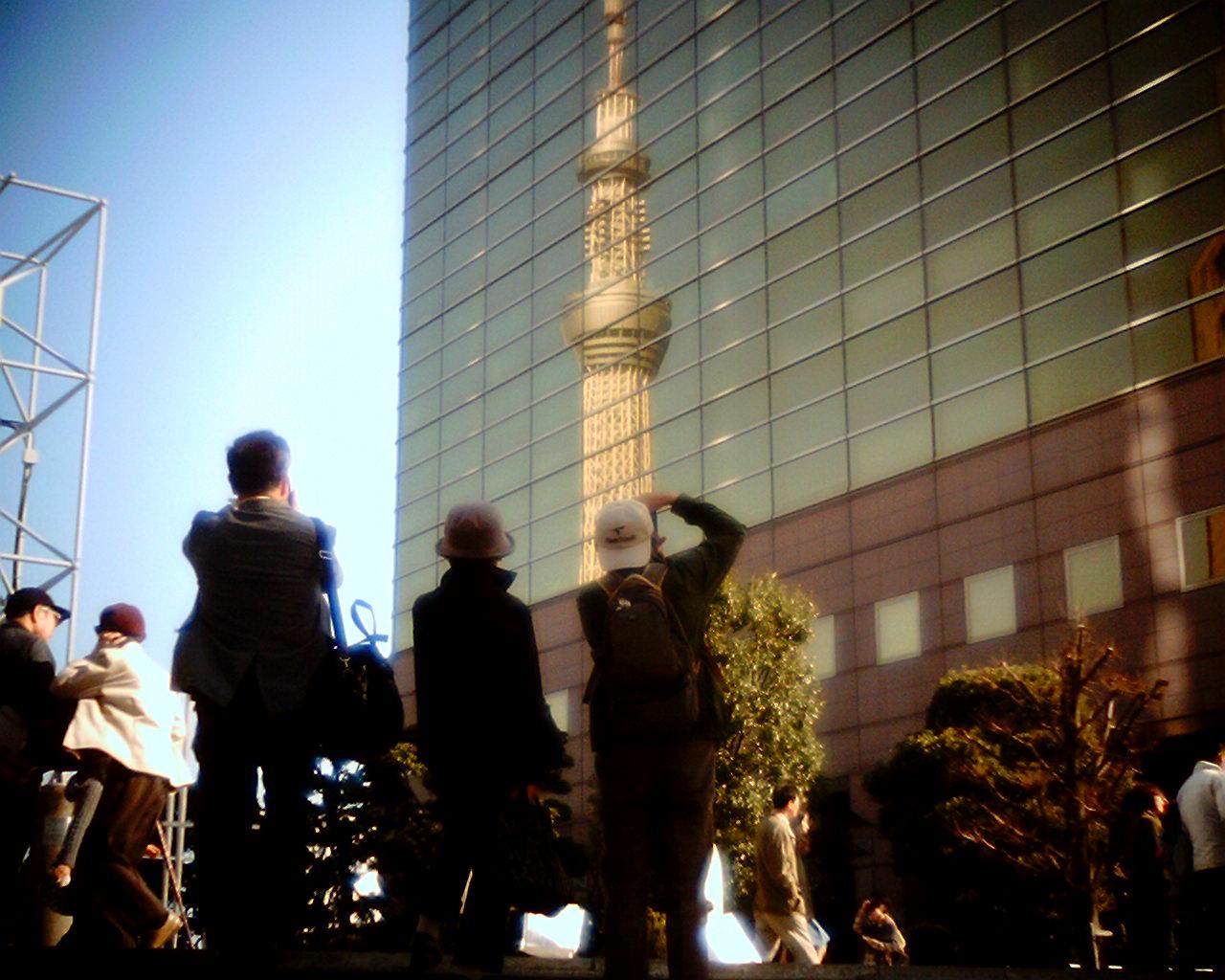 映るスカイツリーを撮る人々